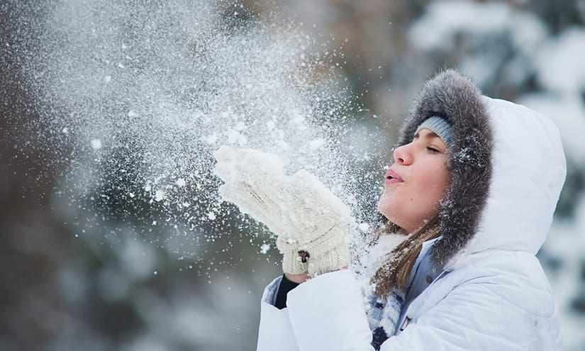 Frau pustet Schnee weg