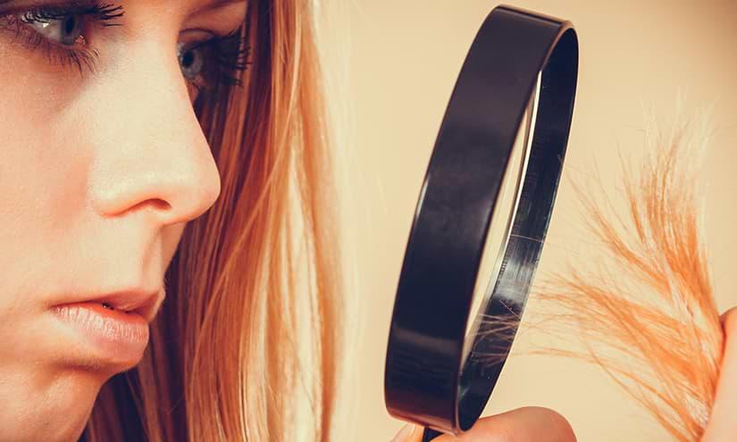 Frau begutachtet ihre Haarspitzen